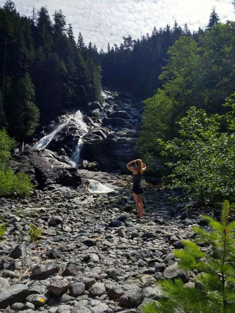 Woman stands in front of water cascading down granite rockface
