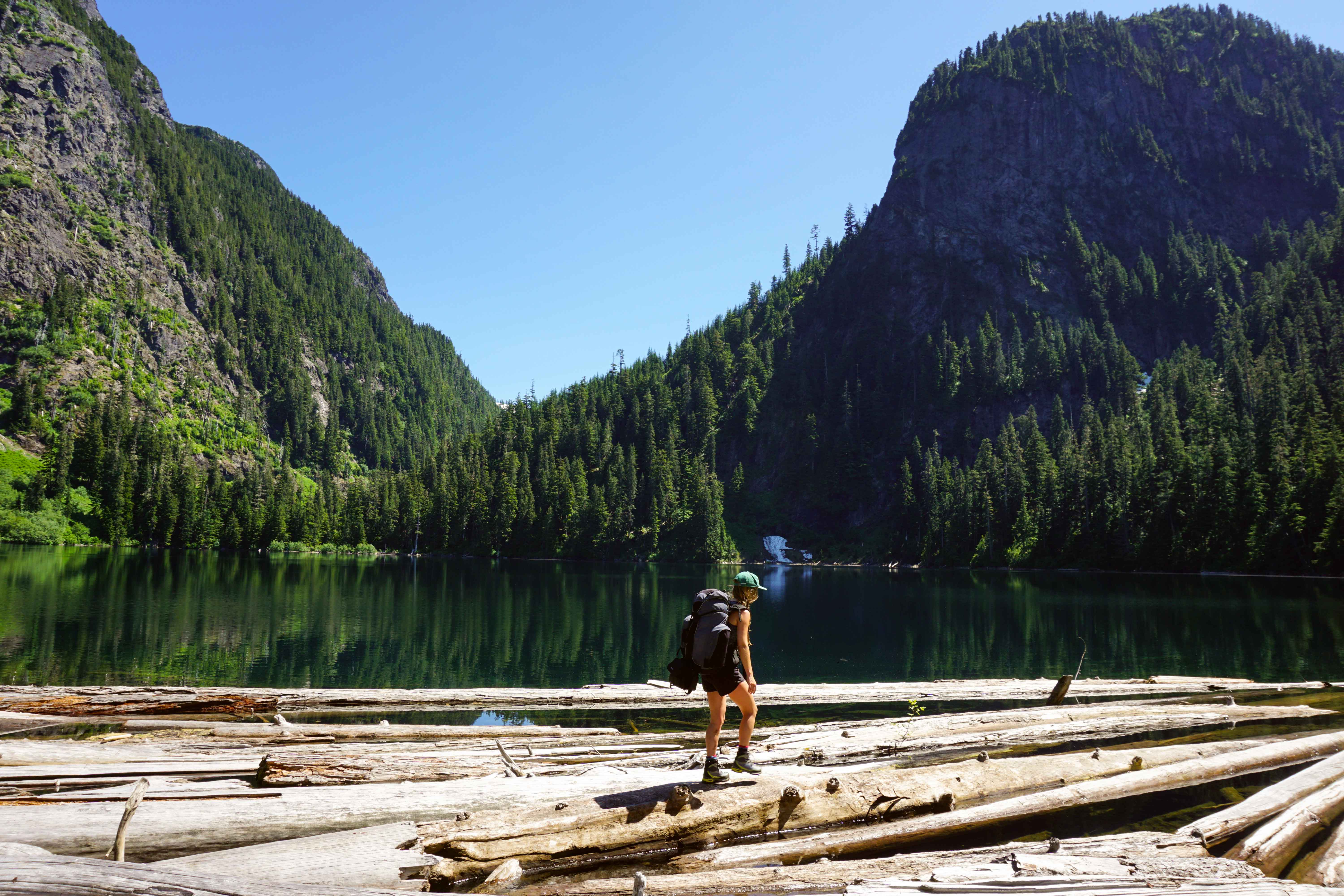 Woman walks across logs on Deeks Lake