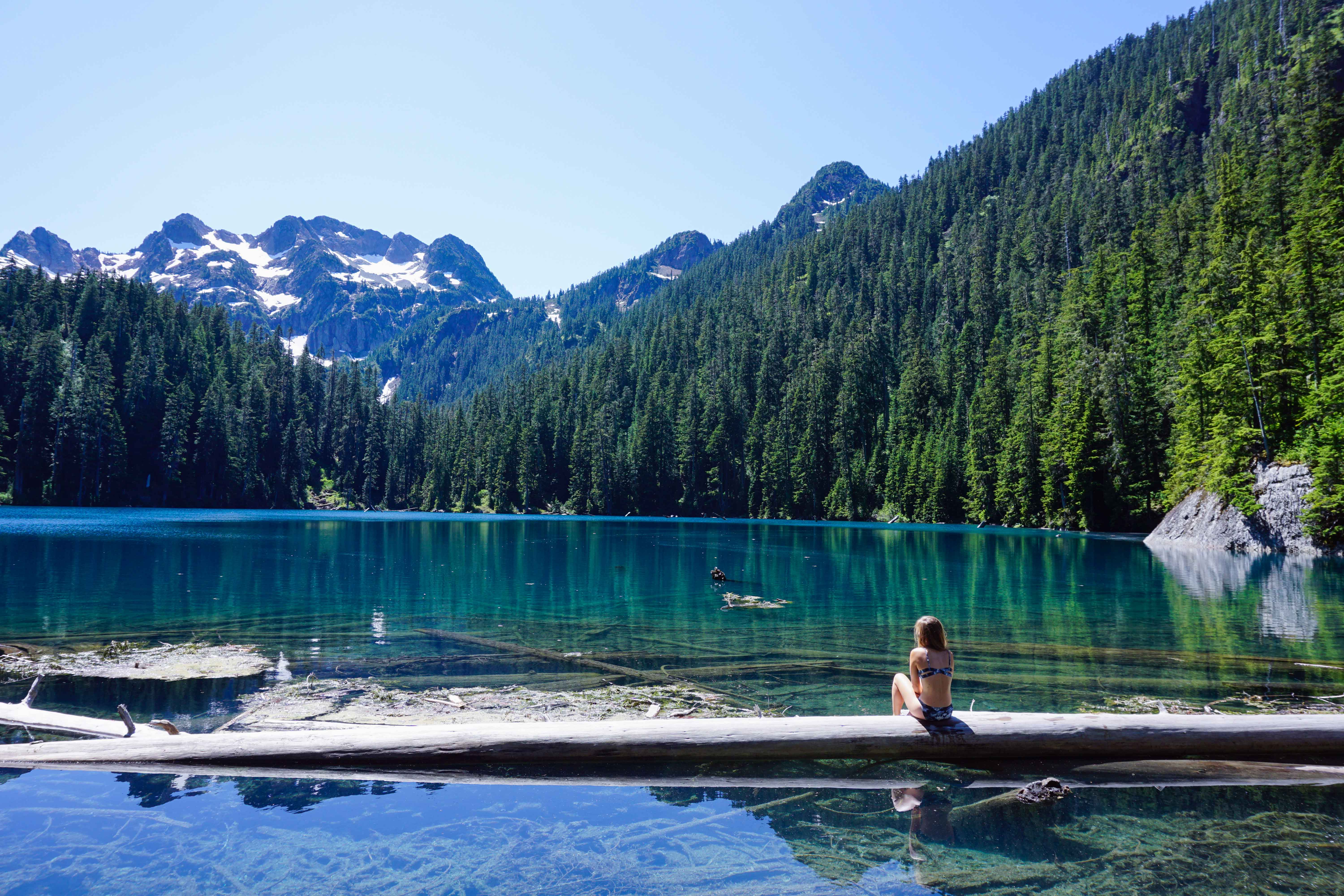 Woman looks across blue lake and mountains