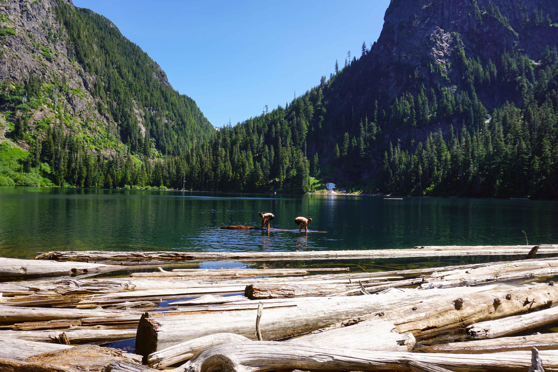 Two men balance on a log in a lake
