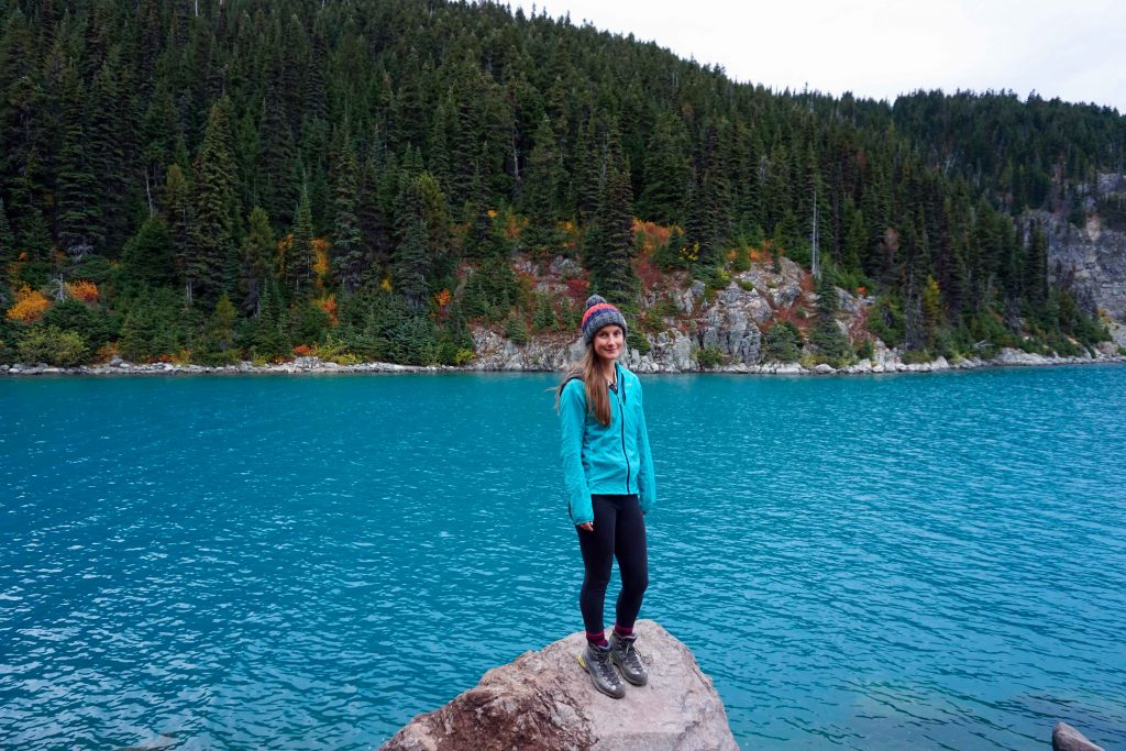 Woman stands on rock in front of blue lake