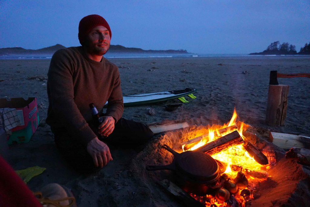 Man cooks using a beach fire