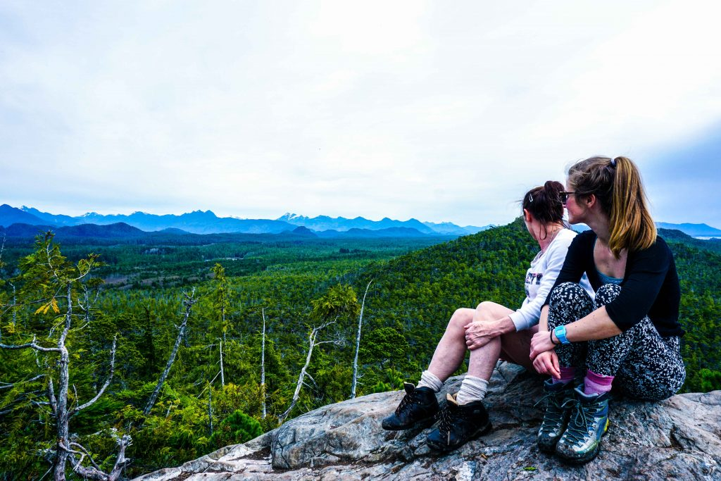 Two women look across rainforest from high vantage point