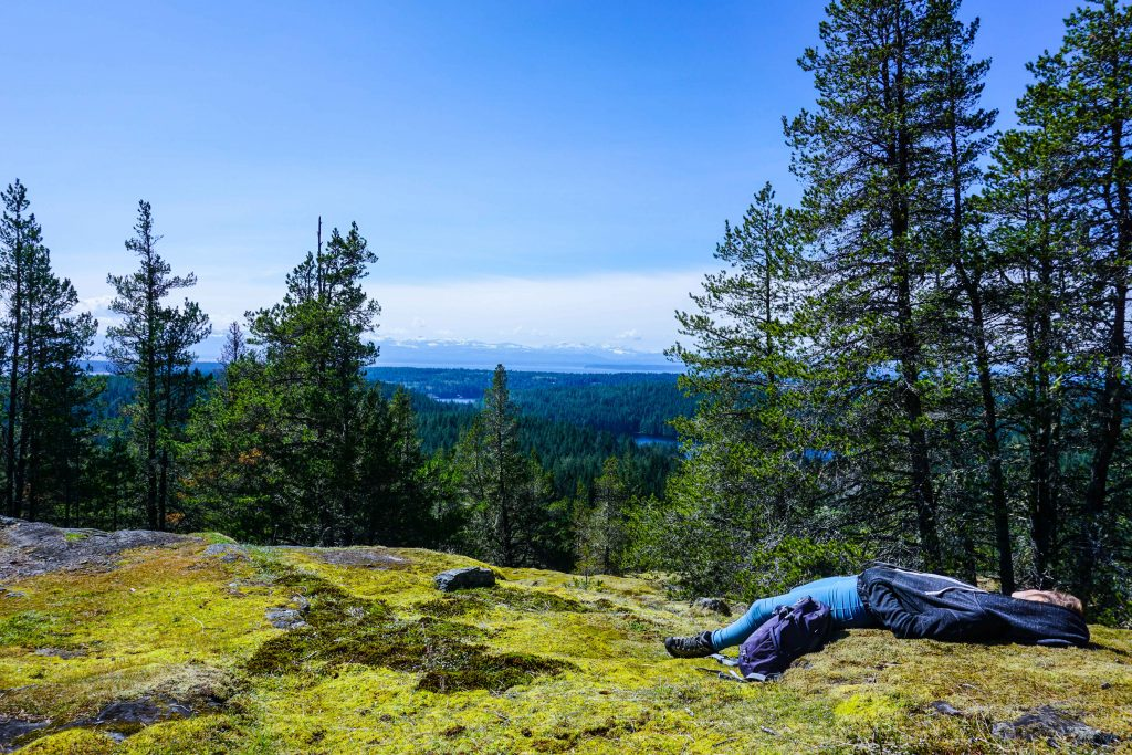 Woman sleeps on mossy rocks