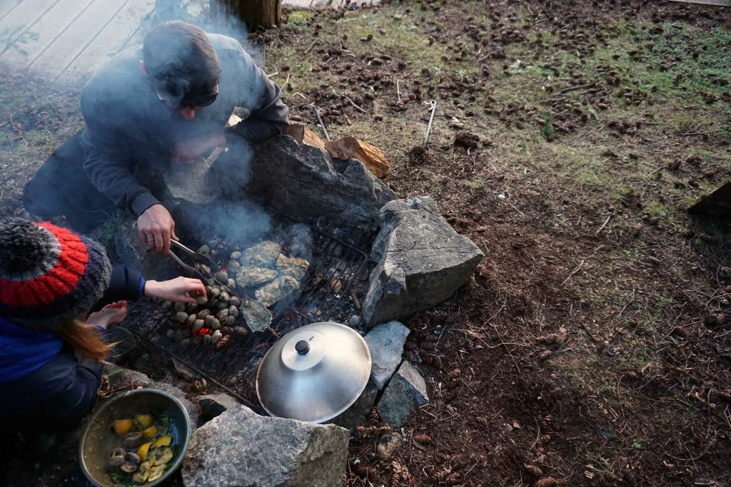 Man and woman cook oysters and clam on an outdoor fire