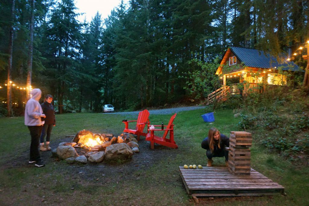 Three people playing Jenga near a campfire