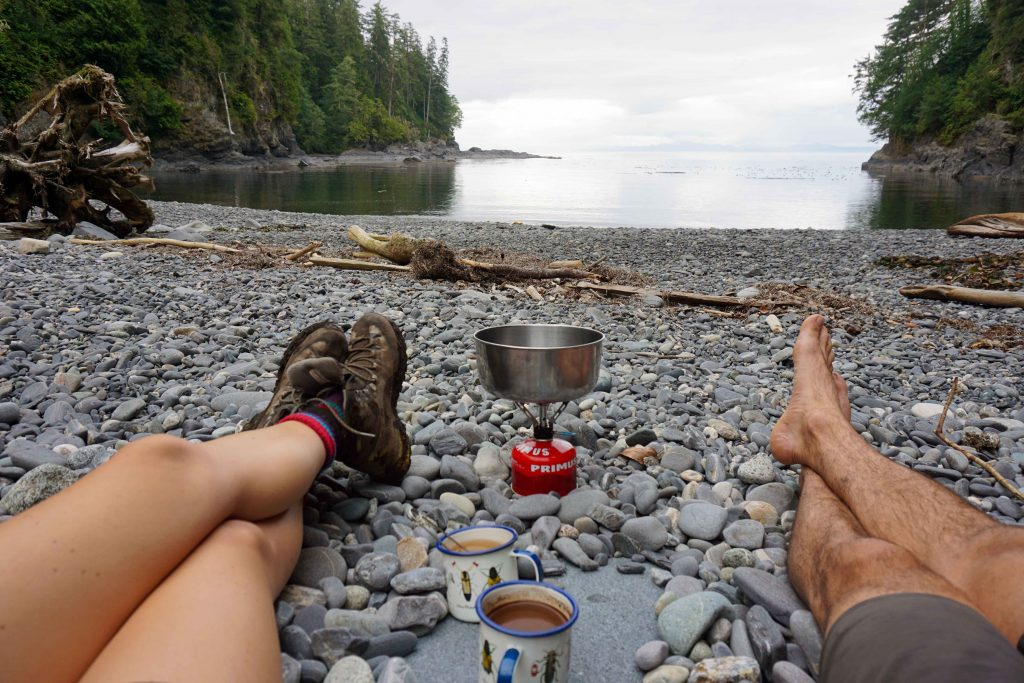 Two people making tea on a portable stove on a stone beach