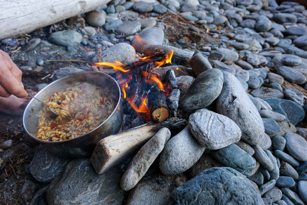Bowl of food cooks over a campfire