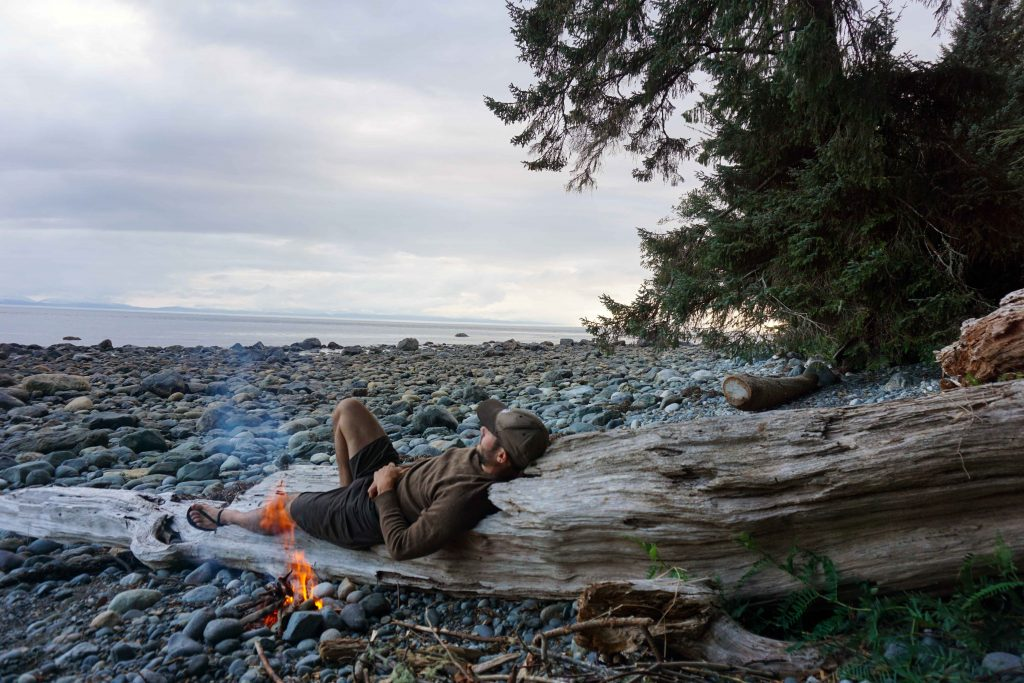 Man lies on beach log next to campfire