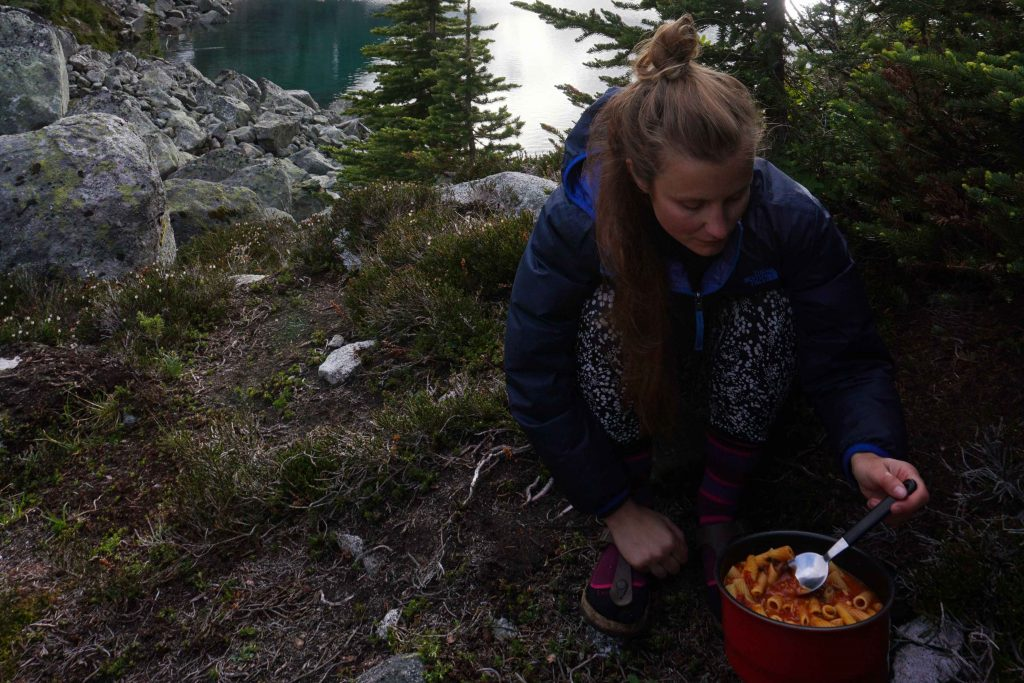 Woman outside cooks pasta in red saucepan