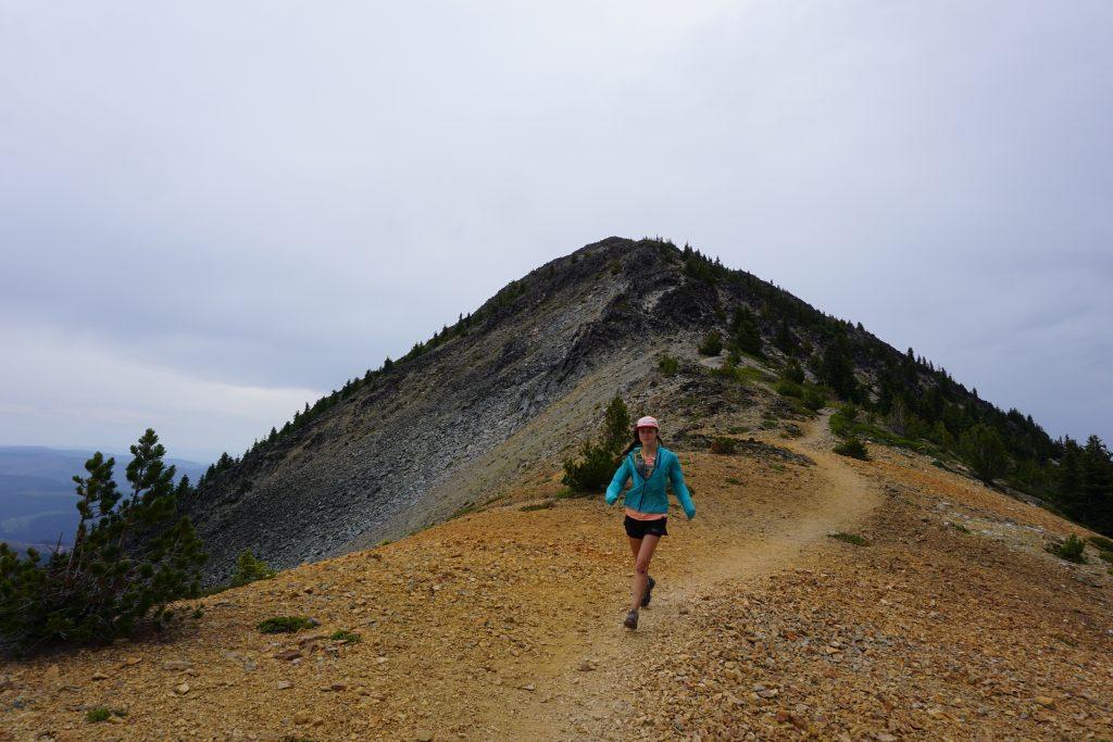 Woman runs down mountain ridge
