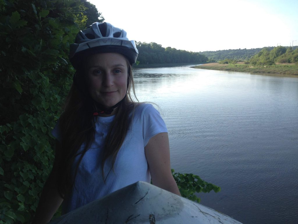 Woman in cycling helmet next to river