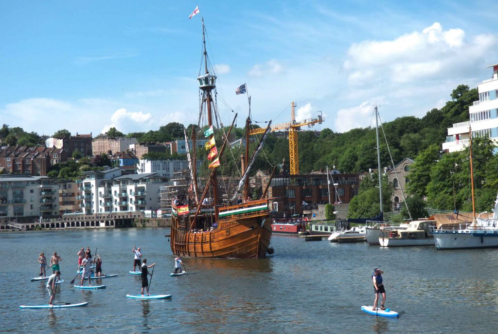 Ship sails down harbour surrounded by paddle boarders