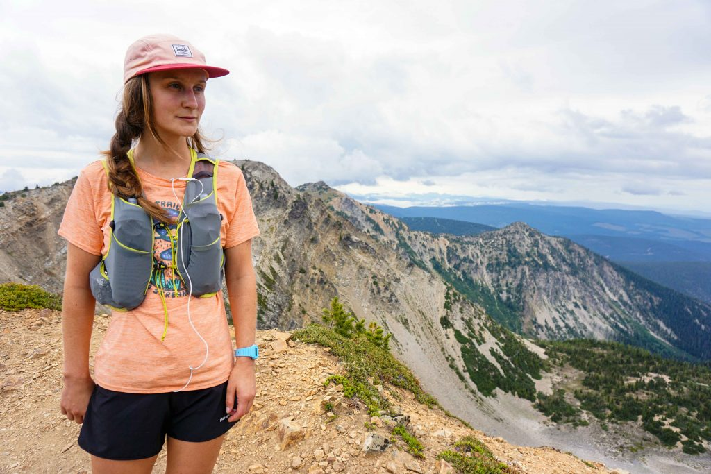 Woman stands on mountain wearing trail running vest