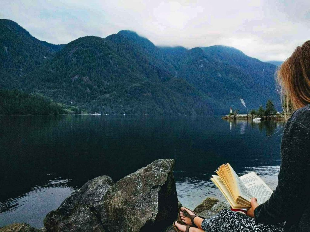 Woman reads book next to calm sea