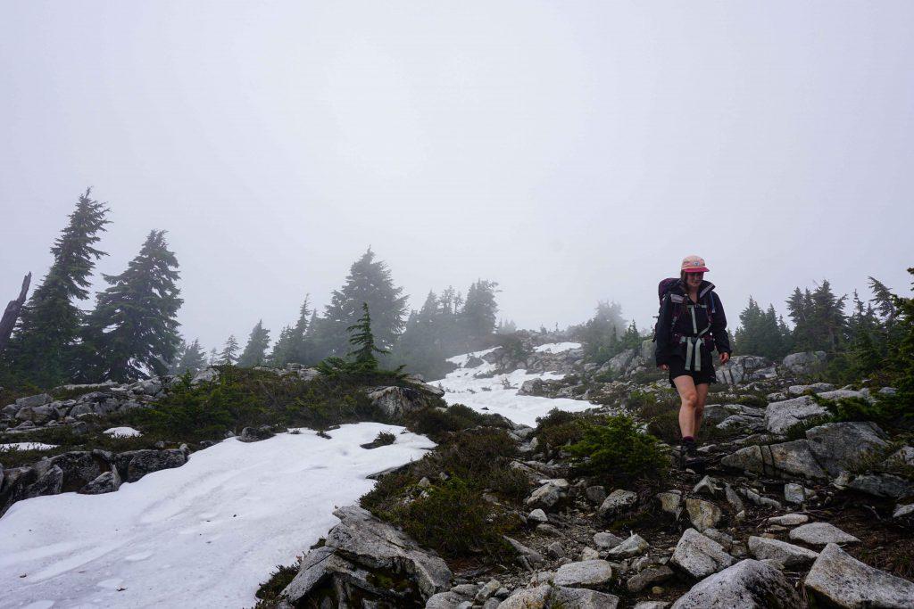 Woman walks along snowy rocky ridge