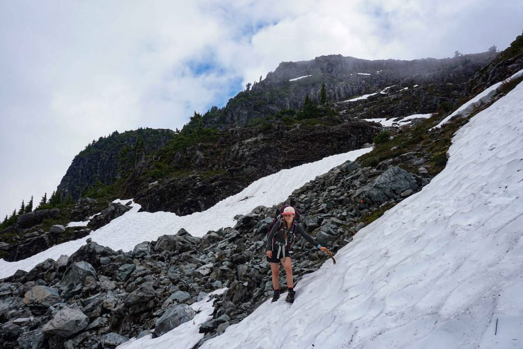 Woman traverses snowy boulder field