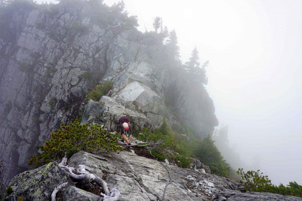 Woman scrambles up mountainside
