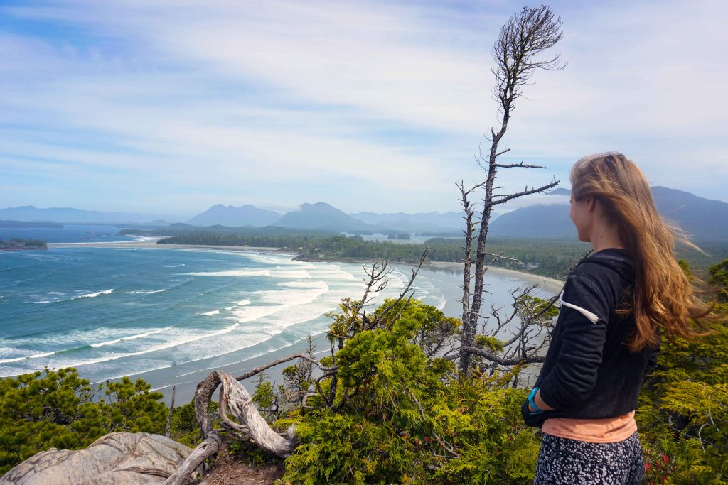 Woman on top of hill looks across sandy beach and sea with waves rolling in