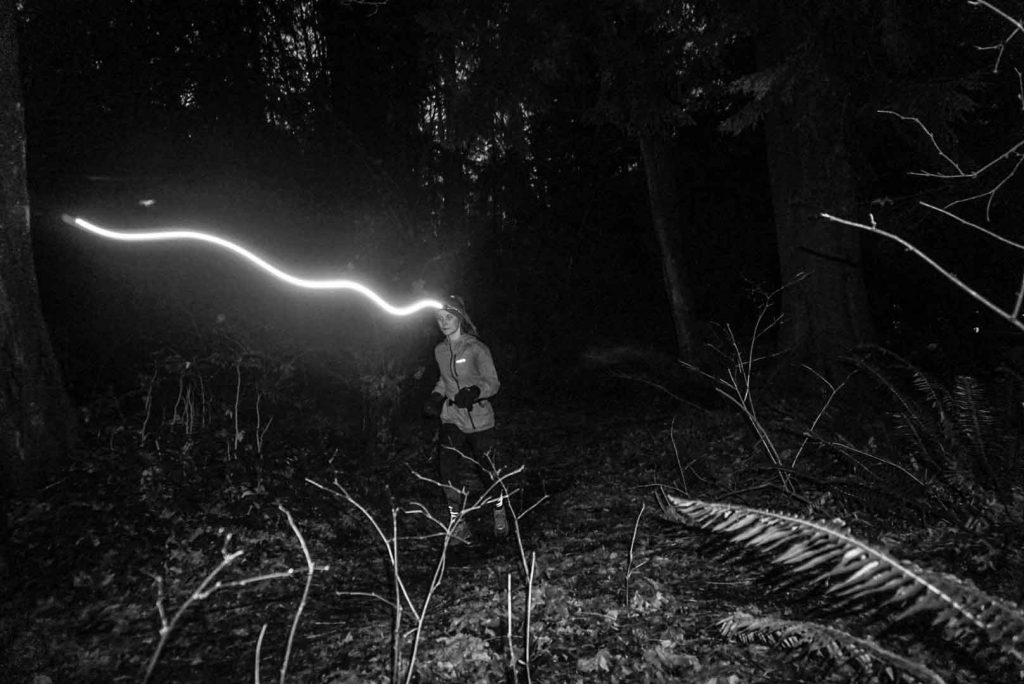 Woman trail running at night with head torch illuminated