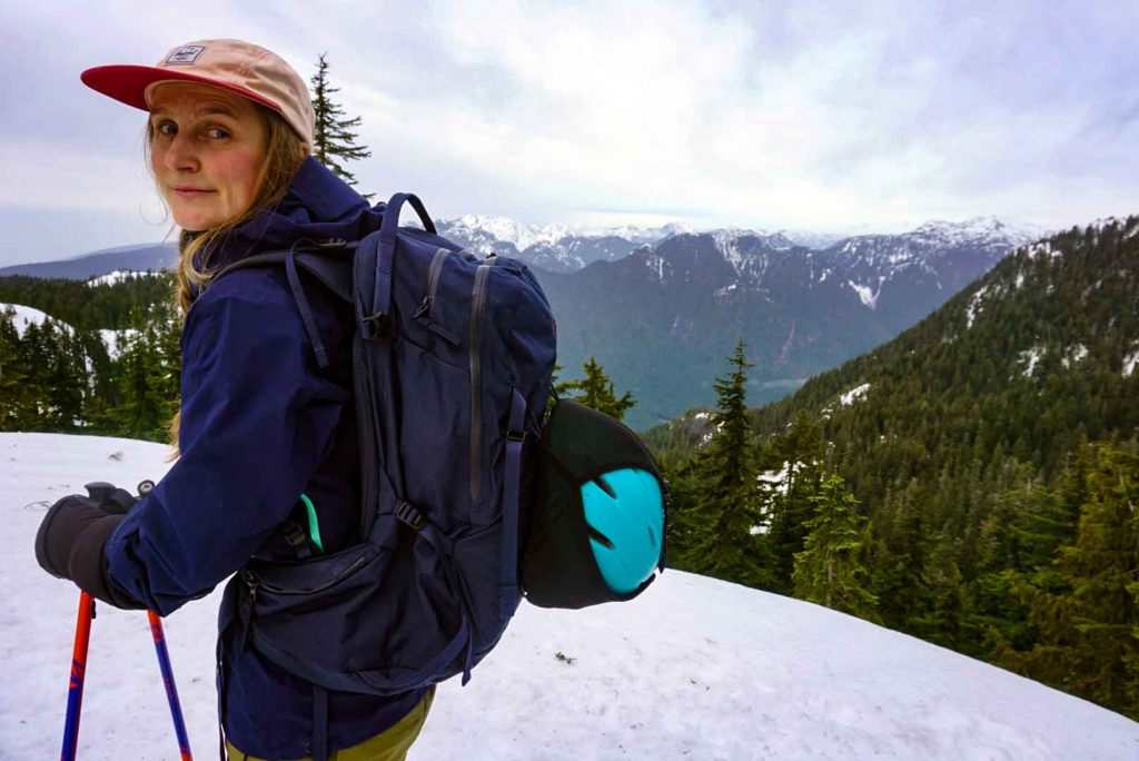 Woman in snowy mountains wearing the blueNorrøna Lyngen 35L Ski Touring Pack