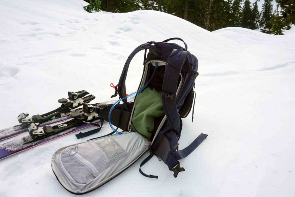 Open backpack on snowy ground