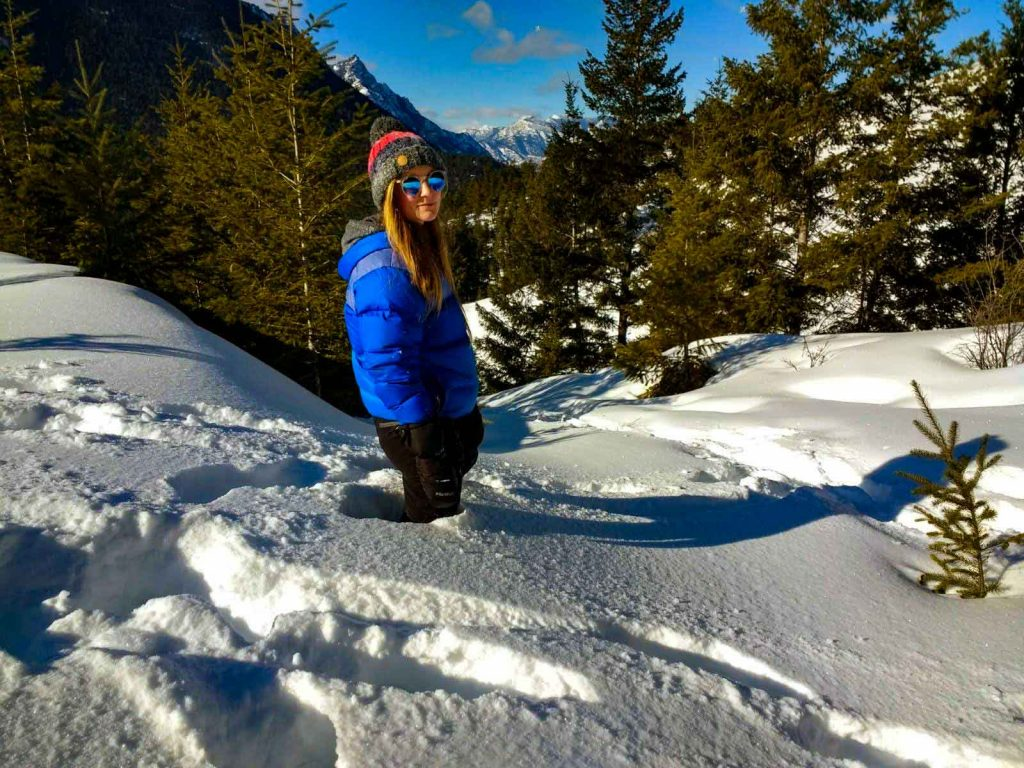 Woman in blue coat and bobble hat stands in deep snow