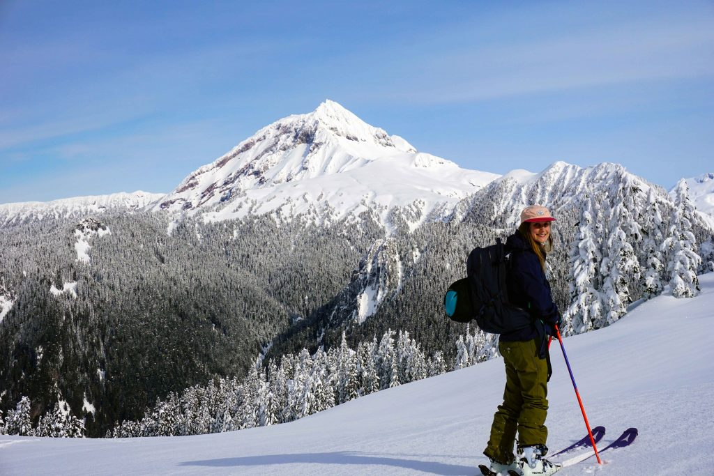 Woman on skis stands on snowy hill with mountains in the distance