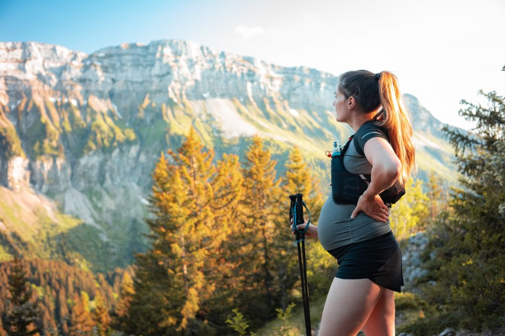 Pregnant hiker holds walking poles and looks across mountains