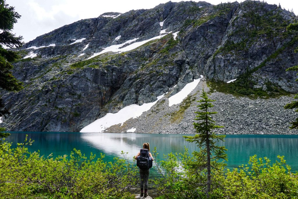 Woman wearing backpack stands in front of turquoise lake