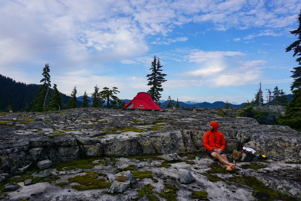 Man in orange top sits next to fire on rocky plateau with rent tent in the background