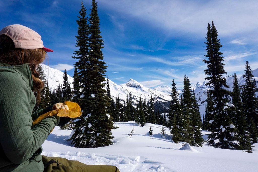 Woman in snowy mountain setting eats sandwich