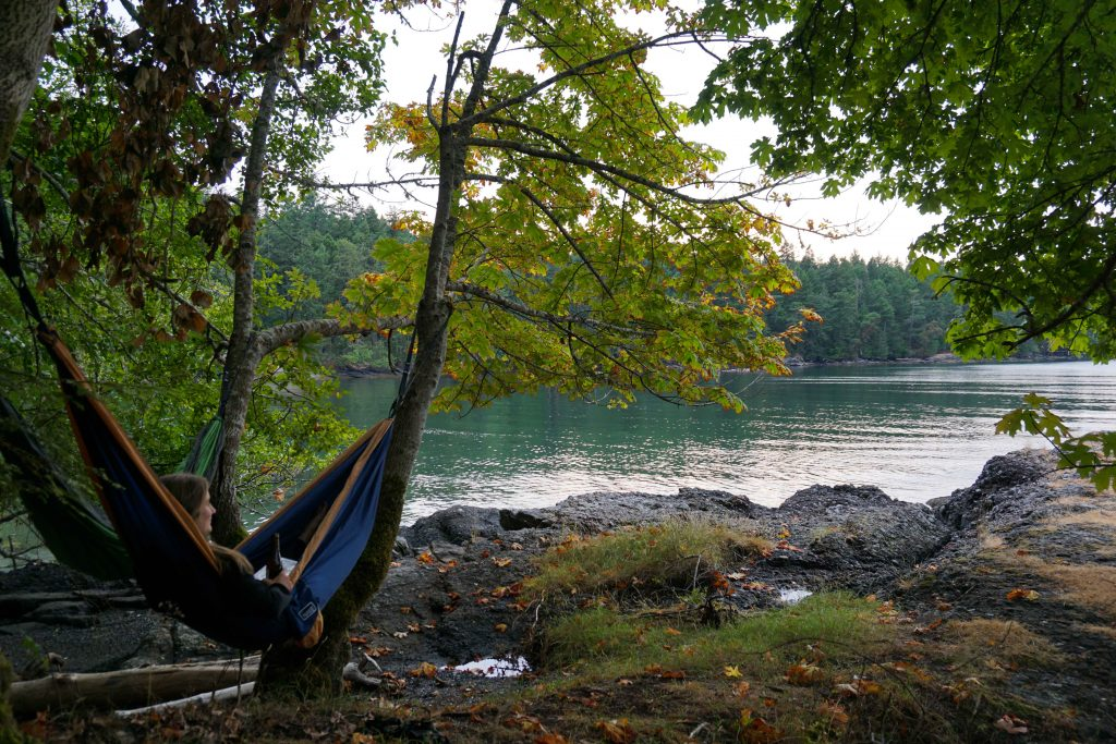 Woman lies in blue hammock next to sea and forest
